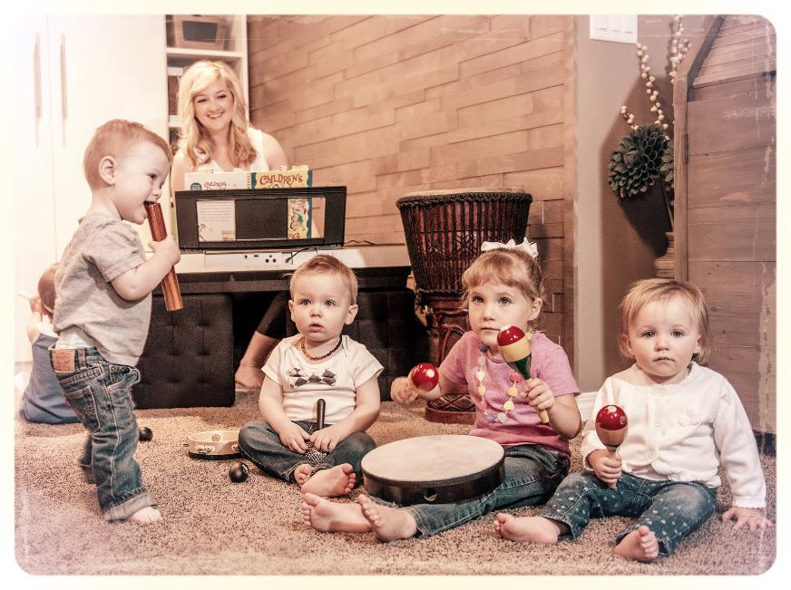 Alison Seipp teaching a music class to four babies/toddlers playing instruments.